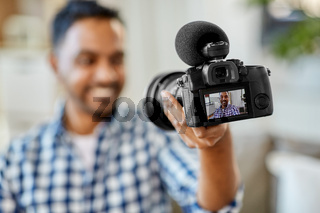 male video blogger with camera blogging at home