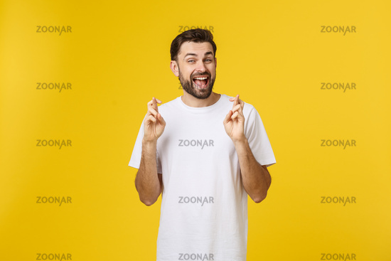 Young man making a wish isolated on yellow background