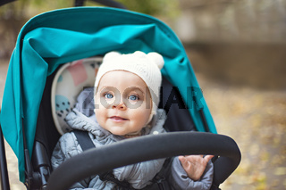 Happy cute baby in a stroller looking out and laughing in the park