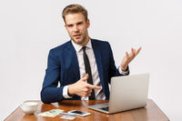 Business, success and corporate concept. Good-looking young businessman discuss company, pointing laptop display as consulting employee, on table coffee cup, money, credit card and smartphone