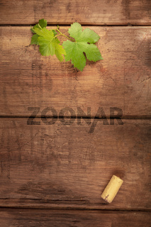 A vine leaf and a wine cork, shot from the top on a dark rustic background with a place for text