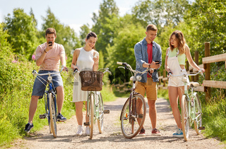 couple with bicycles and smartphone in summer