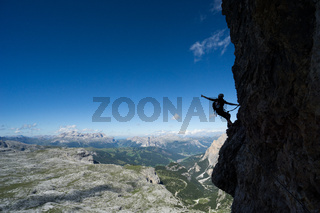 attractive blonde female climber in silhouette on a steep Via Ferrata pointing to the sky