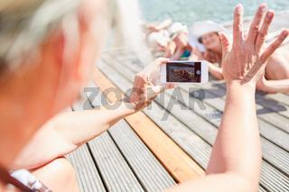 Frau mit Smartphone fotografiert ihre Freunde