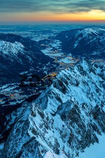 Tagesanbruch auf dem Gipfel der Zugspitze mit Blick auf das erleuchtete Garmisch Partenkirchen und i