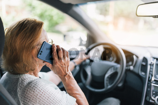 Elderly woman behind the steering wheel of a car using her phone