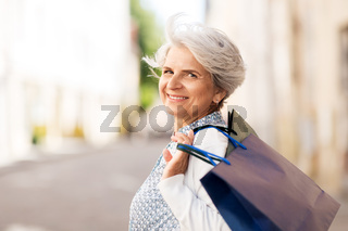 senior woman with shopping bags in city