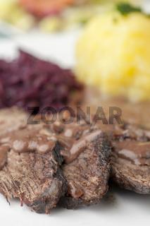 rheinischer Sauerbraten mit Rotkohl auf einem Teller