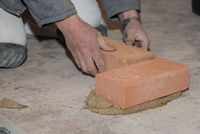 Handwerker mauert Ziegelwand - Nahaufnahme Maurer