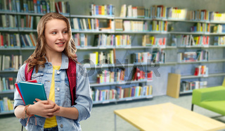 teenage student girl with books at school library