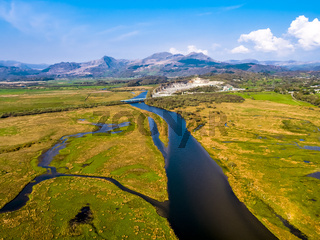 Aerial view of the Glaslyn Marshes close to the railway with the Snowdonia mountain range national park in background - Porthmadog, Wales - United Kingdom