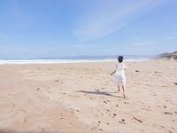 Girl in wedding dress running along the beach