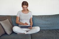 Junge schwangere Frau mit Tablet auf dem Sofa