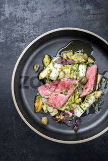 Modern barbecue dry aged sliced fillet steak with asparagus potato salad as top view on a plate with copy space