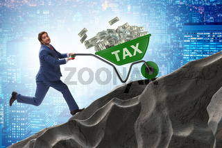 Businessman pushing tax wheelbarrow uphill