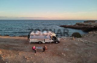 Aerial above view middle aged couple sitting on folding chairs  near recreational vehicle camper trailer on the rocky coast of Mediterranean Sea. Husband play guitar for wife resting after long road