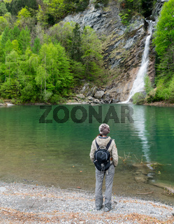 woman hiker looking at a beautiful waterfall and colorful swimming pond in green spring forest landscape