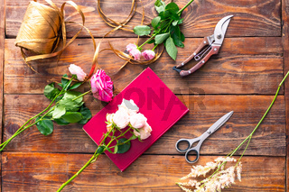 The workplace of the florist to work. Top view. Making floral decorations. Flowers on a old wooden table. Tools and accessories florists need for making up a bouquet.
