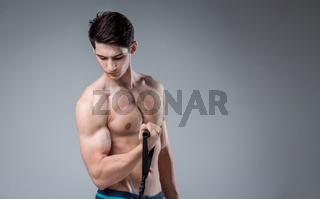 Muscular fitness young male antique perfect muscles six packs of abs and bare chest. Bodybuilder model trains with a stretching elastic against a dark background in the studio. Workout training gym
