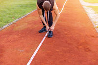 Man tying shoes on the race track