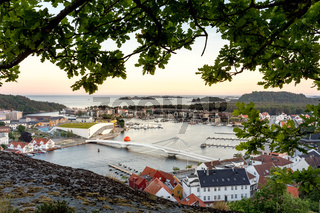 Mandal, Norway - june 2018: Mandal, a small town in the south of Norway. Seen from a height, with a cliff and an oak tree in the foreground.