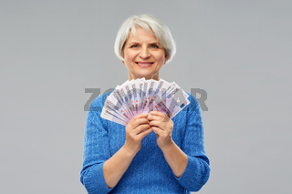 senior woman with hundreds of euro money banknotes