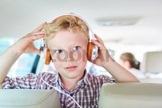 Junge mit Kopfhörern im Auto hört Musik