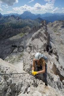 attractive female climber on a steep Via Ferrata in the Italian Dolomites