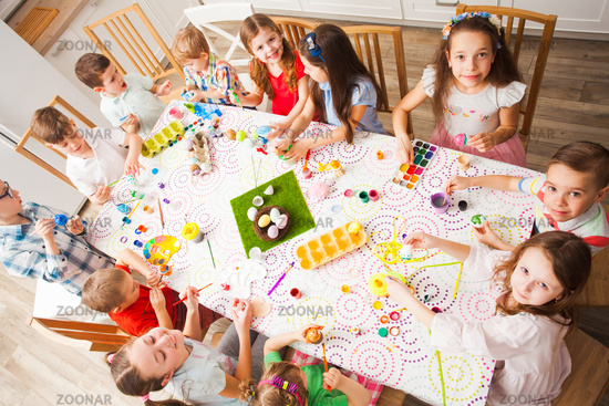 Group of children painting Easter eggs in the kitchen