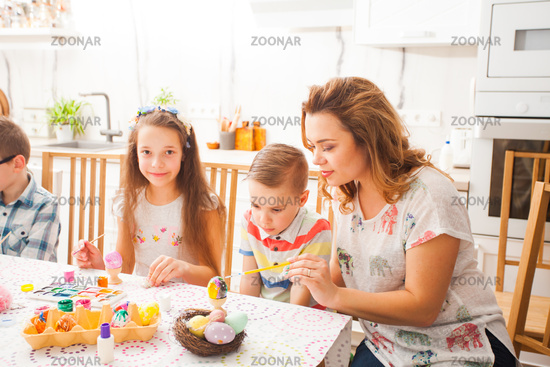 Mom and children painting Easter eggs at the table