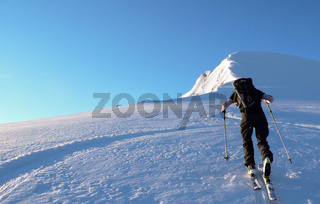 backcountry skier hiking to a remote alpine mountain peak under a blue sky in fresh powder snow