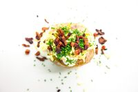 Baked potato with cheese and bacon. Top view