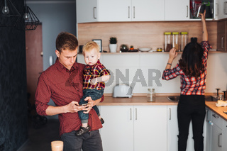 Dad, mom and little son in the kitchen