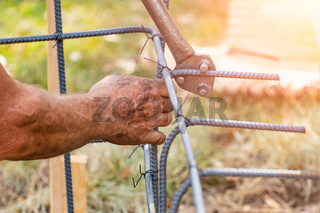 Worker Using Tools To Bend Steel Rebar At Construction Site