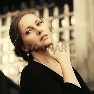 Happy beautiful fashion woman in black blouse walking in city street