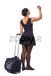 Back view of stylishly dressed black woman with suitcase makes photos on the camera.