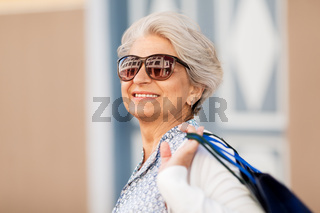 senior woman in sunglasses with shopping bags