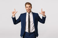 Surprised and glad, excited smiling bearded businessman, male entrepreneur in suit, showing product banner, pointing fingers up and look camera with delighted grin, standing white background