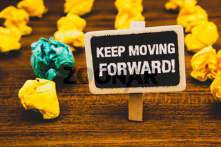 Text sign showing Keep Moving Forward Motivational Call. Conceptual photo Optimism Progress Persevere Move Blackboard with letters wooden floor blurry yellow paper lumps green lob.