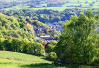 tilt and shift effect photo of the town of hebden bridge in west yorkshire with blurred fields and trees surrounding the town