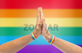 hands with gay pride wristbands make high five