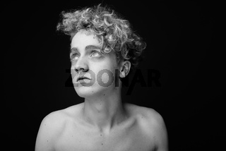 Skinny young man with curly hair shirtless against gray backgrou