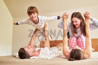 Eltern spielen mit ihren Kindern morgens im Bett