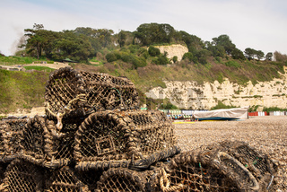 Empty crab pots piled up on a pebble beach with back drop of chalk cliffs
