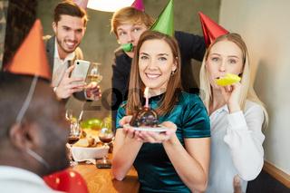 Freunde auf Party werden mit Kuchen  fotografiert