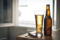 A bottle and a glass of beer and a corkscrew on wooden surface with blurred background and cinematic color grading