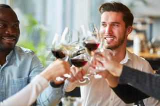 Freunde stoßen an mit Wein im Restaurant