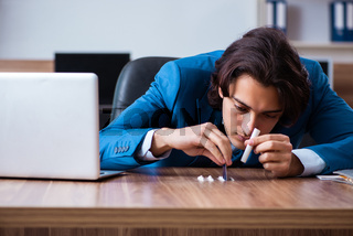 Young man having problems with narcotics at workplace