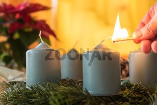 erste Kerze am Adventskranz mit Streichholz anzünden - Nahaufnahme