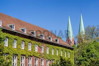 Backsteinhaus mit Hausbegrünung und die Türme der Marienkirche in Lübeck, Deutschland